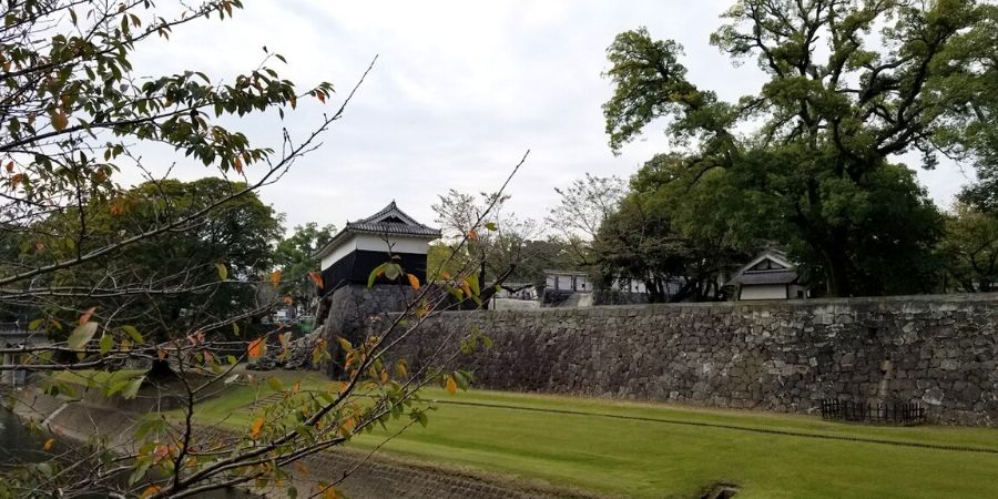 View of Kumamoto Castle complex, stone walls and moat from the perimeter of the castle premise.