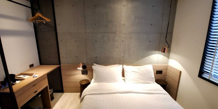 A standard double room at Monka Hotel featured a modern wooden headboard, wood side table and rose gold lamps.