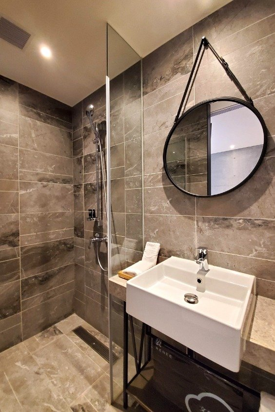 The ensuite bathroom has floor to ceiling tiles and modern bathroom fixtures.