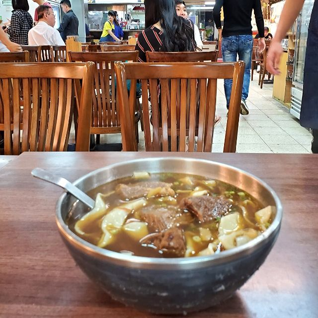 A bowl of homemade beef noodles at 老山東牛肉麵 (Lao Shandong Homemade Noodles) has handmade ribbon noodles and big chunks of beef.