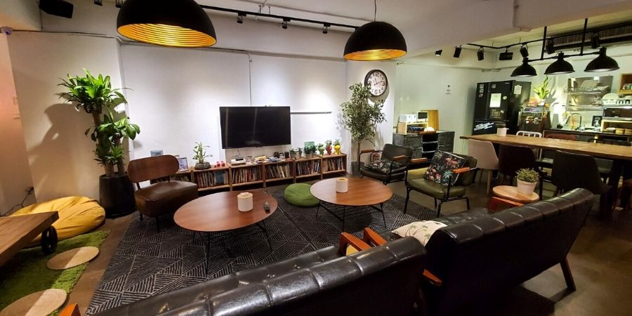 The spacious common area at We Come Hostel has a sitting area and a functional kitchen.